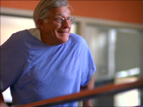 Senior male patient in hospital gown walking slowly in rehab / physical therapy + smiling