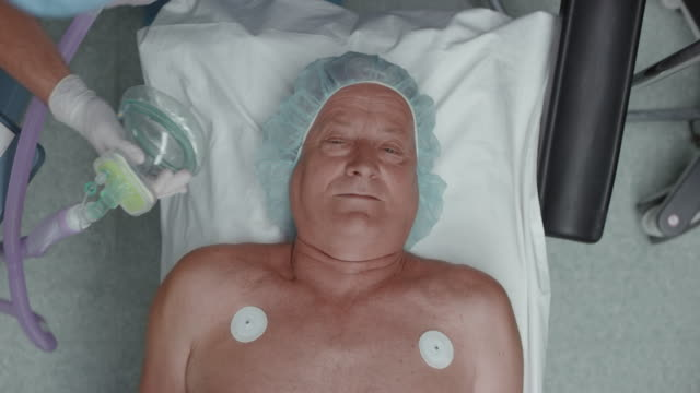 senior male patient inhaling anesthetic via inhalation mask before surgery - anesthetic stock videos and b-roll footage