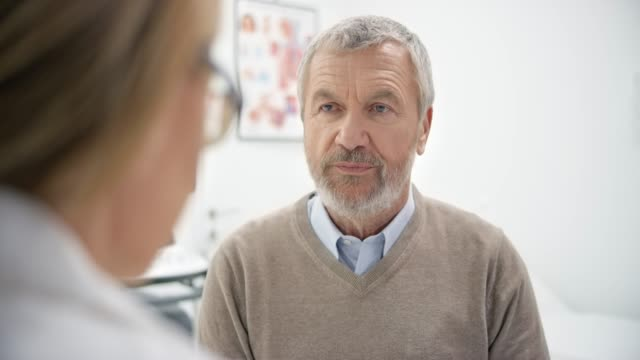 Senior male patient listening carefully to his doctor