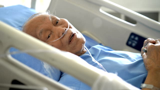 senior male patient looking at camera while he is resting on hospital bed - weakness stock videos & royalty-free footage