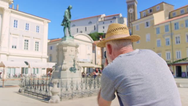 senior male photographer taking a photograph of the statute in a town square - monument stock videos & royalty-free footage