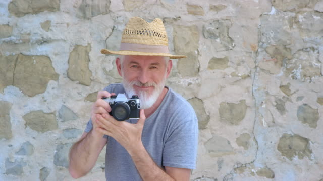 pov senior male photographer with a summer hat and a grey beard taking a photo - sun hat stock videos & royalty-free footage