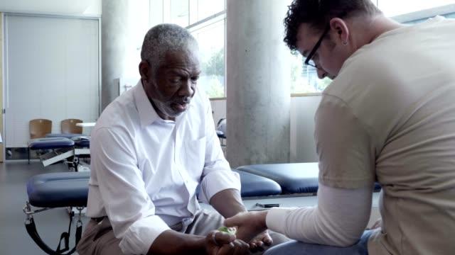 vidéos et rushes de le physiothérapeute masculin aîné aide le patient avec la réadaptation de main ou de poignet - poids pour la musculation