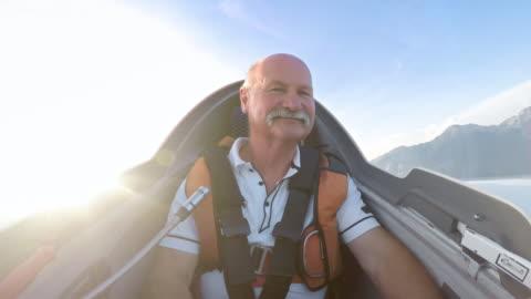 vídeos y material grabado en eventos de stock de piloto hombre senior ld disfrutando del vuelo en su vuelo en un día soleado - deporte de riesgo