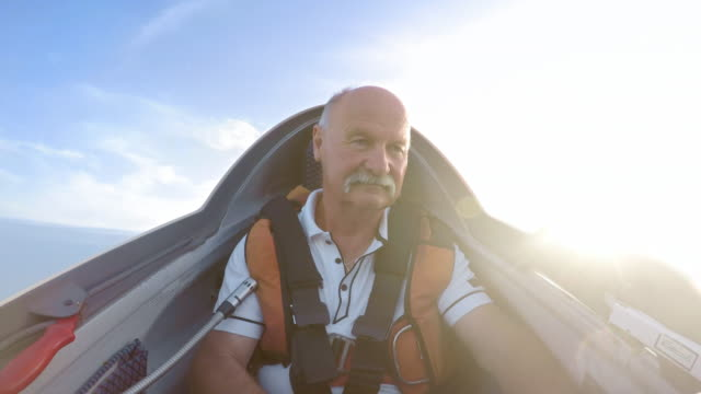 ld senior male pilot flying the glider on a sunny day - stunt stock videos & royalty-free footage