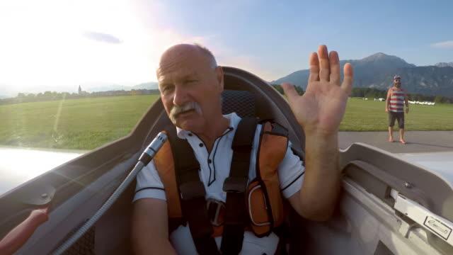 ld の高齢男性のグライダーのコックピットにパイロット入ると離陸する前に手を振って - 空気力学点の映像素材/bロール