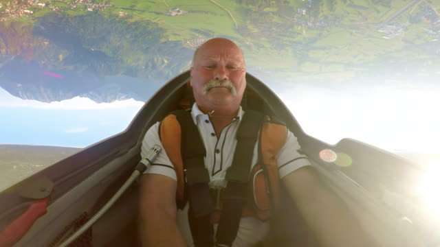 speed up: senior male pilot in the cockpit smiling whole looping in the glider across the sunny sky - balding stock videos & royalty-free footage