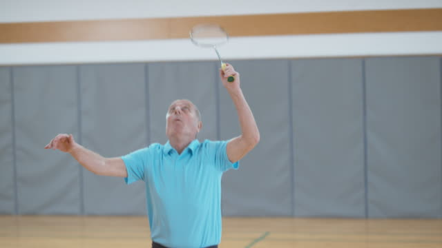 Senior male player playing indoor badminton