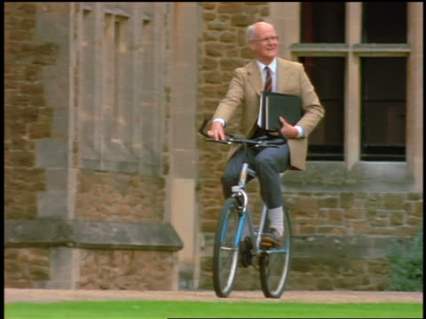 PAN senior male professor riding bicycle + holding books past building / England