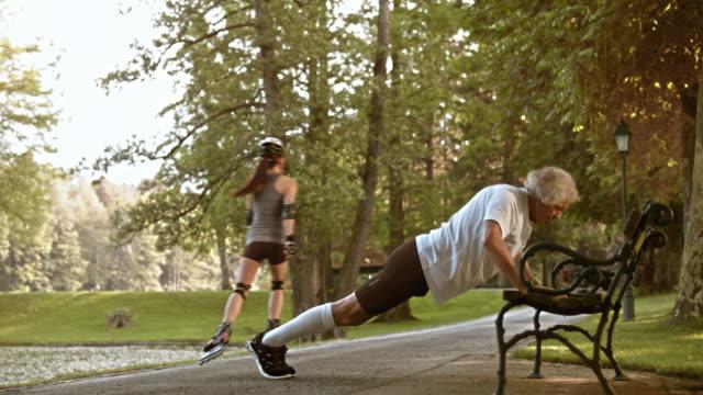 stockvideo's en b-roll-footage met ds senior mannelijke loper doet push ups op een bankje - oefeningen met lichaamsgewicht