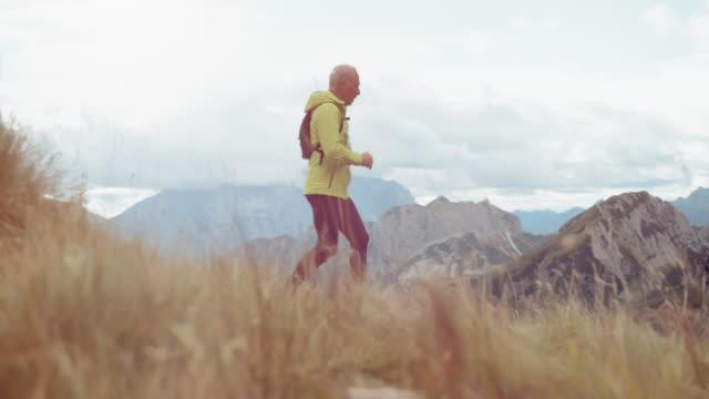 山の斜面をマラソン SLO MO DS シニア男性ランナー