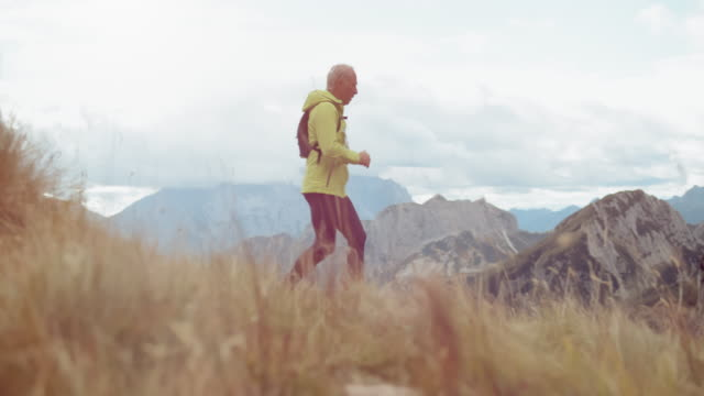 SLO MO DS Senior male runner running a marathon down the mountain slope