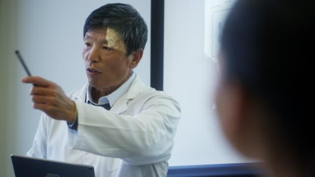 ボードルームで説明するシニア男性科学者 - 説明する点の映像素材/bロール