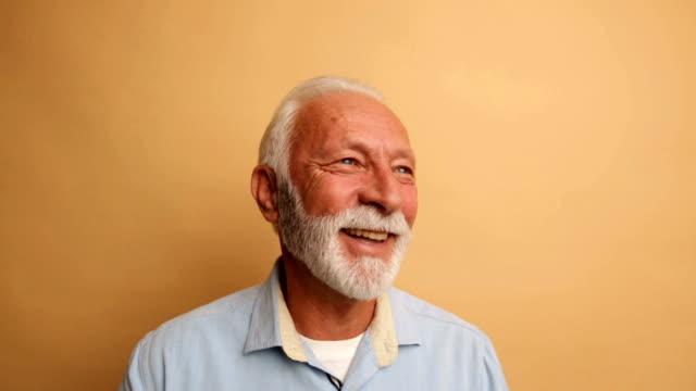 senior male smiling in studio - orange background stock videos & royalty-free footage