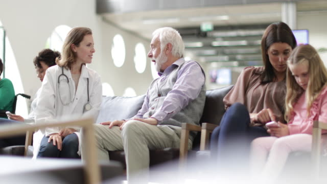 senior male talking to doctor in a crowded hospital waiting room - waiting room stock videos & royalty-free footage