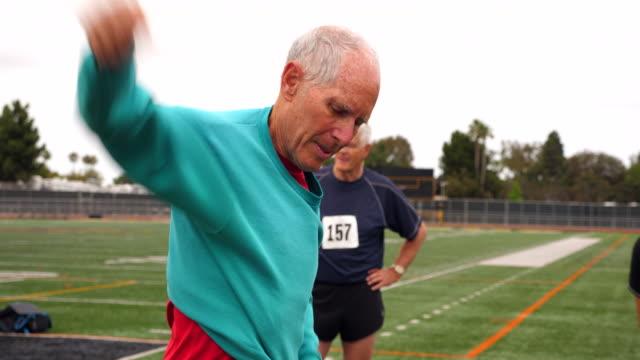 ms senior male track and field athlete putting sweatshirt on after track meet - sweatshirt stock videos & royalty-free footage