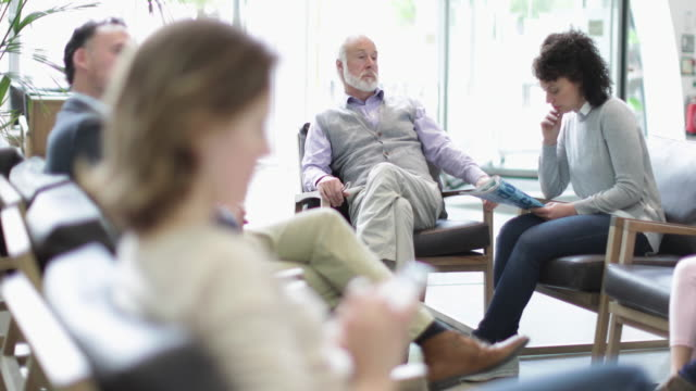 senior male waiting in a crowded hospital waiting room - waiting room stock videos & royalty-free footage