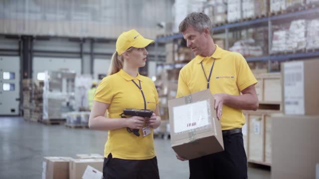 DS Senior male warehouse supervisor explaining something to a female employee holding a scanner