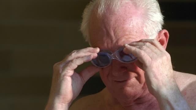 vídeos de stock e filmes b-roll de cu senior man adjusting his swimming goggles and holding ball / seattle, washington, usa - só um homem idoso