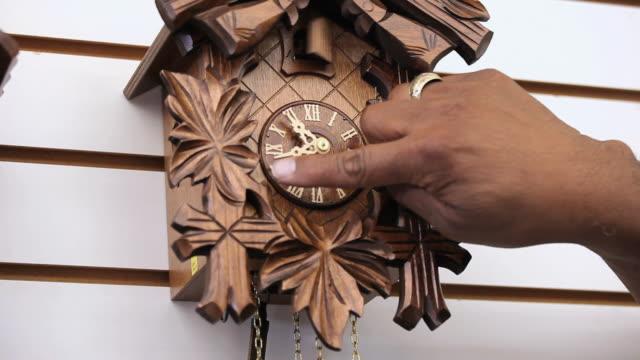 cu senior man adjusting time on antique cuckoo clock / richmond, virginia, usa.  - romersk siffra bildbanksvideor och videomaterial från bakom kulisserna
