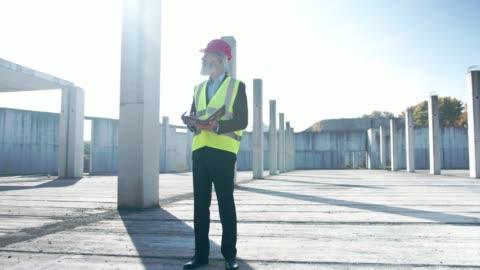 senior man, en ingenjör, stående fortfarande på en tom byggarbetsplats - stål bildbanksvideor och videomaterial från bakom kulisserna