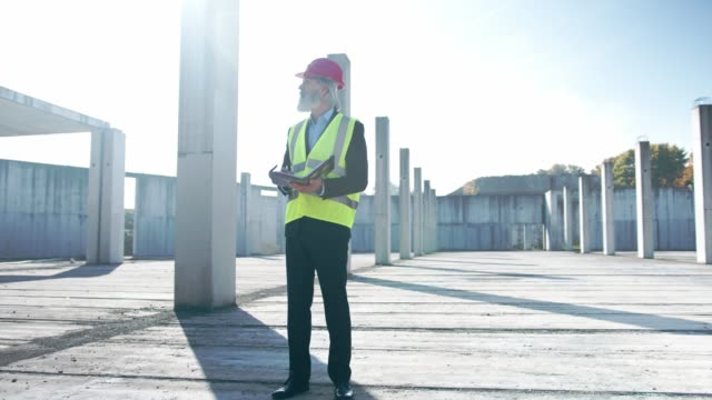 senior man, an engineer, standing still on an empty construction site - steel stock videos & royalty-free footage