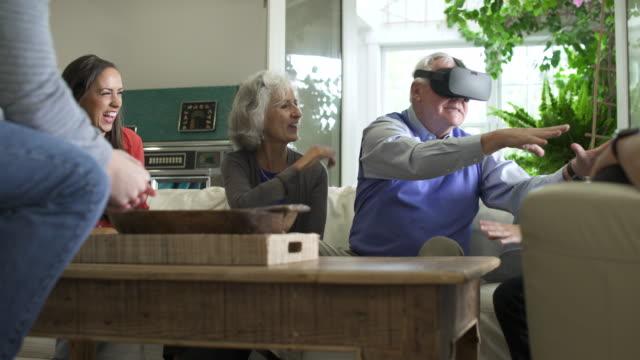 Senior man and family using virtual reality headset.
