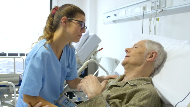 senior man and female nurse communicating in hospital
