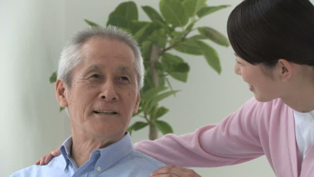 vídeos y material grabado en eventos de stock de senior man and female nurse talking, smiling - servicios sociales