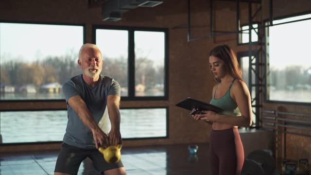 vídeos y material grabado en eventos de stock de hombre mayor e instructor de fitness en el gimnasio - serbia