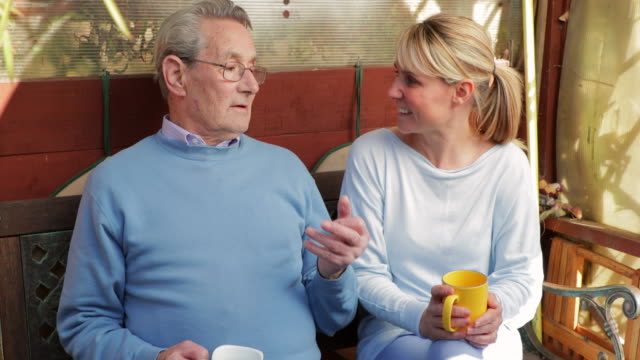 senior man and his carer outside in garden having a hot drink - discussion stock videos & royalty-free footage