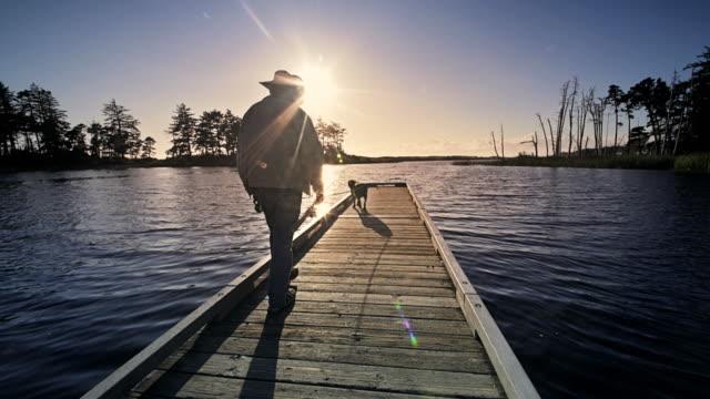 Senior man and his dog fly fishing off dock, Oregon