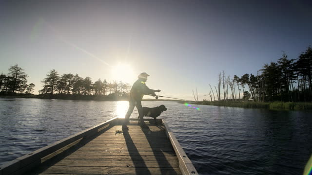 Senior man and his dog fly fishing off dock, Oregon
