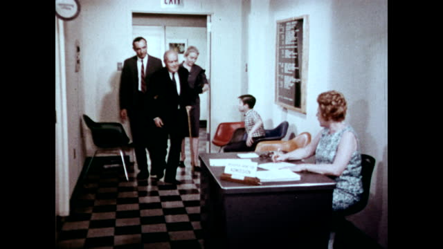/ senior man and his family entering hospital while narrator explains the different parts of medicare / man signing admission forms / admission clerk... - narrating stock-videos und b-roll-filmmaterial