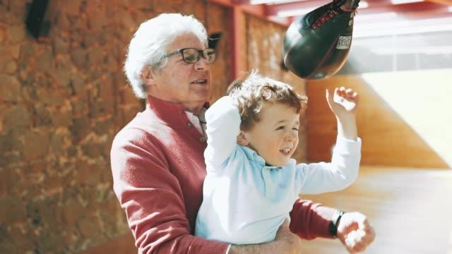 vídeos de stock e filmes b-roll de senior man and his grandson hitting a punching bag - 60 64 anos
