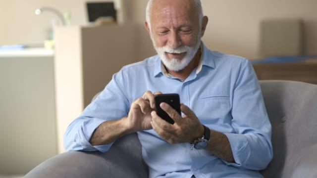 vídeos de stock e filmes b-roll de senior man and his smartphone - confortável