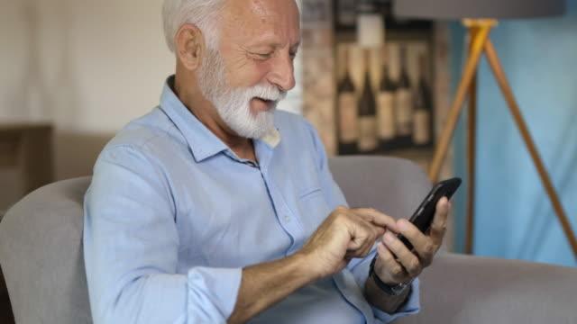vidéos et rushes de homme aîné et son smartphone - 60 64 ans