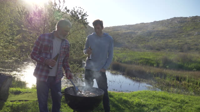 senior man and his son barbecue together in nature - adult offspring stock videos & royalty-free footage