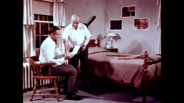 / senior man and his son sitting on his bed discussing the bill from the surgeon / man explains how Medicare will help pay his bill / men go...