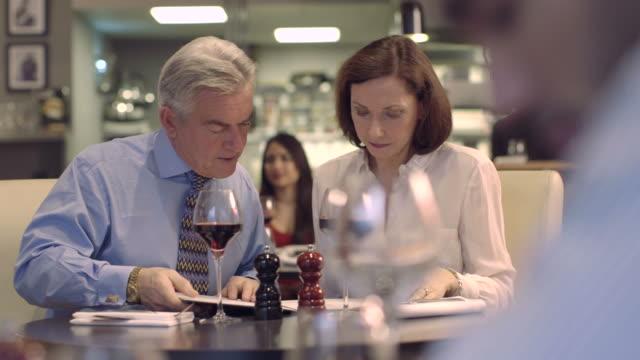 stockvideo's en b-roll-footage met ms pan senior man and mature woman drinking wine in restaurant - overhemd en stropdas