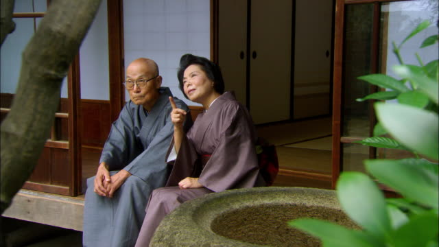 MS Senior man and senior woman sitting side by side at entrance to house/ Tokyo, Japan
