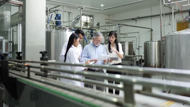 senior man and two young women attentive workers examining a machine in factory - man and machine stock videos & royalty-free footage