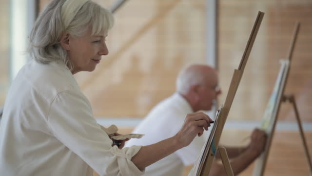 ms pan selective focus senior man and woman drawing on easels in art class / vancouver, british columbia, canada - kunst stock-videos und b-roll-filmmaterial