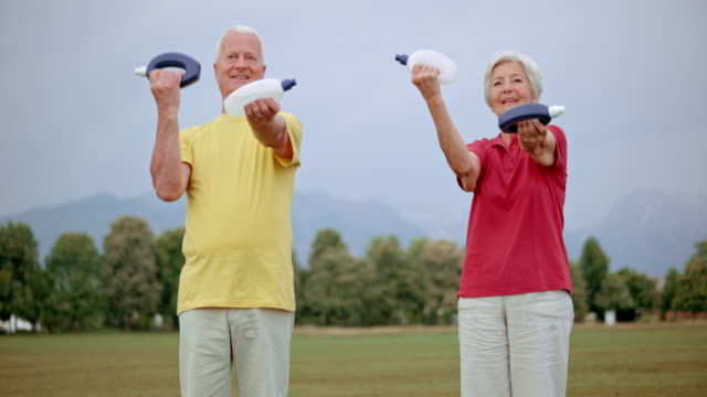 slo mo senior man and woman exercising in park - hand weight stock videos & royalty-free footage