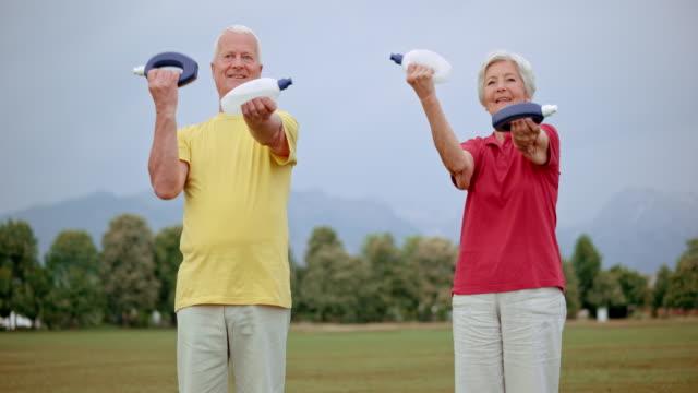 SLO MO Senior man and woman exercising in park