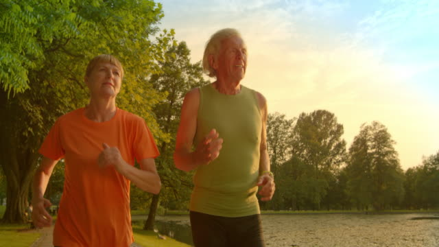 slo mo ts senior man and woman jogging at sunset - vest stock videos & royalty-free footage