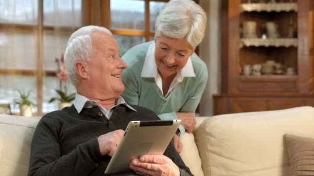 DS Senior man and woman learning to use the tablet