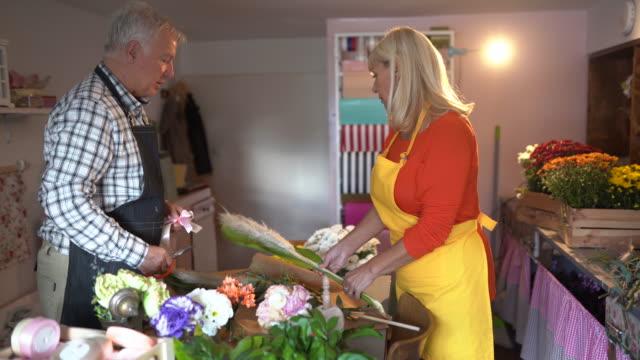 senior man and woman making flower arrangement at flower shop - flower arrangement stock videos & royalty-free footage