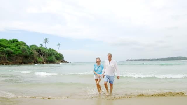 stockvideo's en b-roll-footage met senior man en vrouw op strand hand in hand - 70 79 jaar
