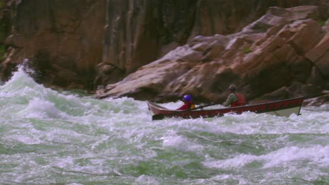 ws ts pan slo mo senior man and woman piloting dory through large rapids / grand canyon, arizona, usa - effort点の映像素材/bロール